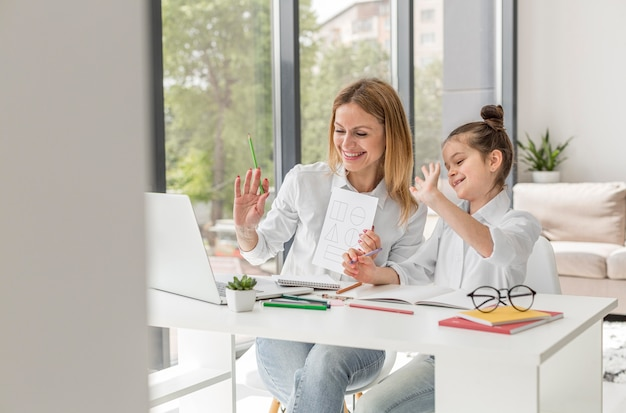 Małej dziewczynki studiowanie z jej nauczycielem indoors