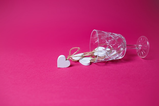 Mali biali drewniani serca w łgarskim wina szkle na różowym tle z kopii przestrzenią.