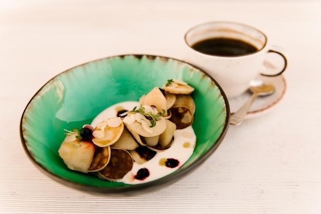 Mali bliny w talerzu z jagodami i domowej roboty kwaśną śmietanką z filiżanką kawy na białym tle, selekcyjna ostrość