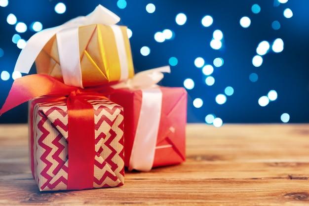 Mali boże narodzenie prezenta pudełka na drewnianym stole przeciw bokeh zaświecają