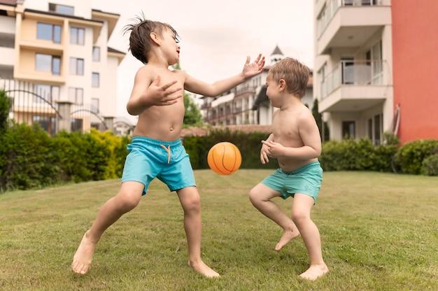 Mali chłopcy bawią się piłką