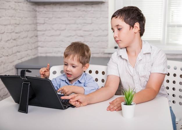 Mali chłopcy biorący udział w kursach online w salonie zostają w domu