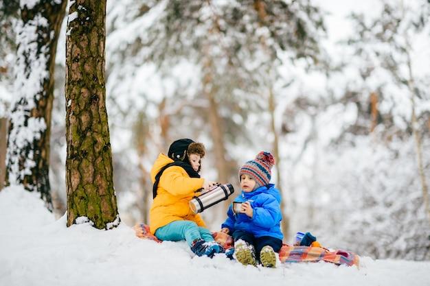 Mali chłopcy mają piknik w zimowym lesie i dzielą się herbatą z termosu.