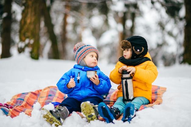 Mali chłopcy mają piknik w zimowym lesie. małe dzieci pije herbatę z termosu w śnieżnym lesie.