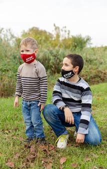 Mali chłopcy noszący maskę ochronną w parku