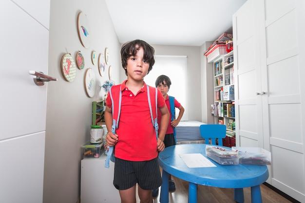 Mali chłopcy stoi z plecakami w pokoju przedszkolnym