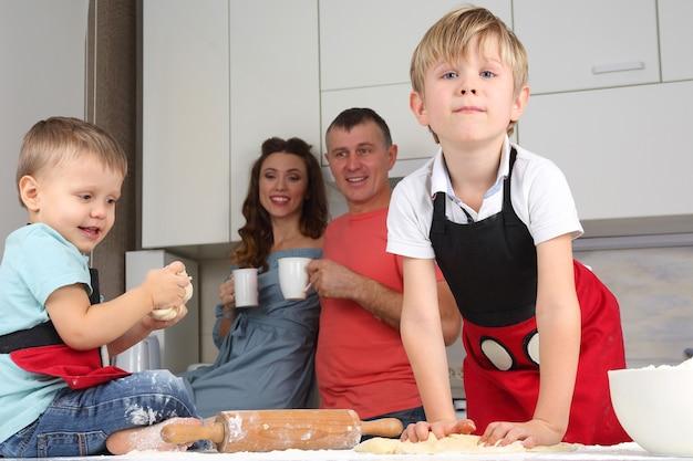 Mali chłopcy wyrabiają ciasto na tle rodziców
