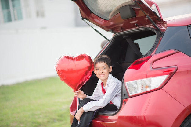 Mali chłopiec siedzi na tylnym drzwi samochodu z balonowym sercem w ręce