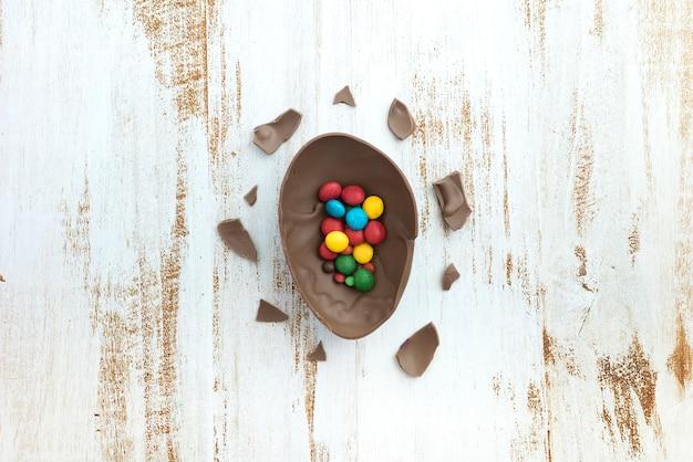 Mali cukierki w otwartym czekoladowym jajku na stole