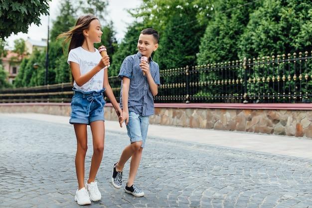Mali i szczęśliwi przyjaciele spacerujący po mieście i jedzący razem słodkie lody.