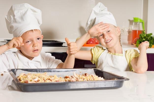 Mali kucharze zmęczeni pieczeniem pysznej pizzy w kuchni.