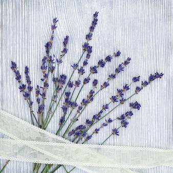 Mali kwiaty lawendy z koronkowym warkoczem na szarym drewnianym tle z copyspace. widok z góry. zapewnia fotografię w stylu