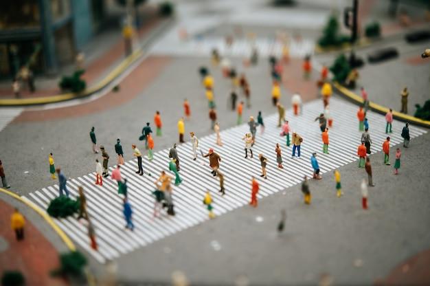 Mali ludzie lub mali ludzie chodzą po wielu ulicach.