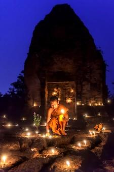 Mali nowicjusze palą świece okolice phra that everyda