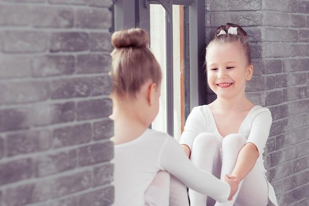 Mali przyjaciele, dzieciaki tańczą balet, siedząc na parapecie i obejmując się, uśmiechając się razem