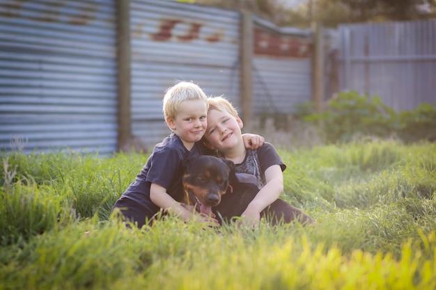 Mali śliczni chłopcy siedzą szczęśliwie na trawie i pozują z psem rottweilera