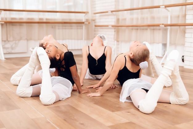 Mali tancerze ćwiczą rozciąganie na podłodze.