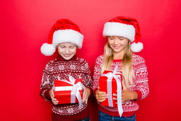 Mali urocze, czarujący krewni w tradycyjnym stroju świątecznym, odizolowani na czerwonej przestrzeni, podekscytowani, patrząc na prezenty, trzymaj je i zgadnij, co jest w środku, ciekawość, życzenie, marzenie, wyobraźnia