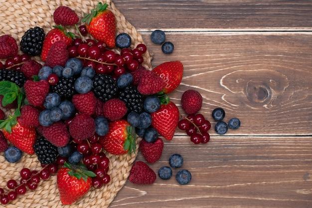 Malinowa jeżyna i jagoda tło na drewnianym stole świeże jagody z bliska