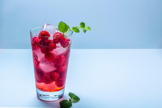 Malinowy koktajl alkoholowy z likierem, wódką, lodem i miętą na białym tle. raspberry mojito. orzeźwiający zimny napój, lemoniada lub mrożona herbata w szklance
