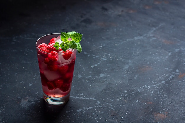 Malinowy koktajl alkoholowy z likierem, wódką, lodem i miętą na ciemnej ścianie. raspberry mojito. orzeźwiający zimny napój, lemoniada lub mrożona herbata w szklance. zamknij się, skopiuj miejsce na tekst, niski klucz