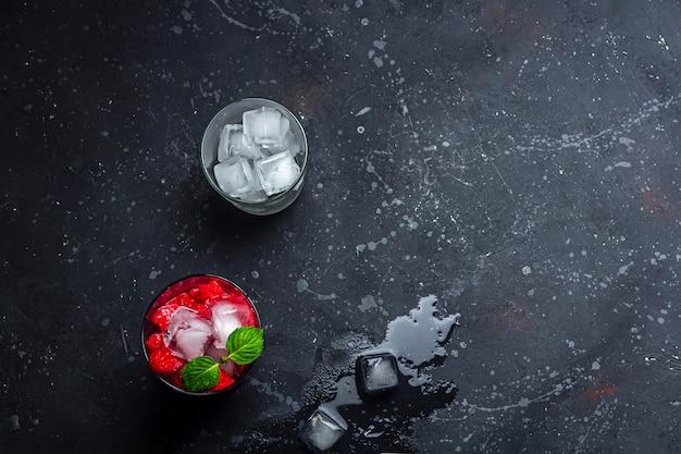 Malinowy koktajl alkoholowy z likierem, wódką, lodem i miętą na ciemnym tle. raspberry mojito. orzeźwiający zimny napój, lemoniada lub mrożona herbata w szklance.