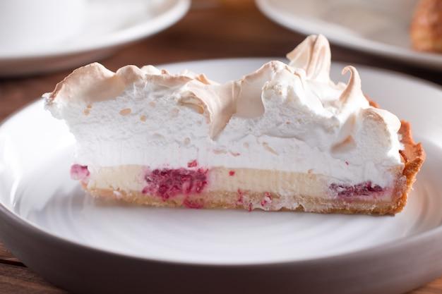 Malinowy tort z białą uwielbianą bezą na drewnianym stole