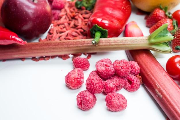 Maliny i inne czerwone owoce i warzywa na białym tle