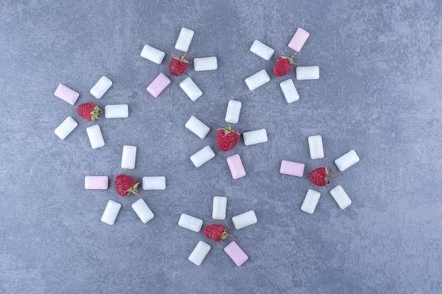 Maliny i tabletki gumy w dekoracyjnych kompozycjach w kształcie kwiatków na marmurowej powierzchni