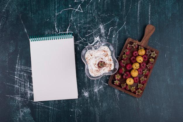 Maliny i wiśnie na drewnianym talerzu z filiżanką lodów i książeczką rachunków