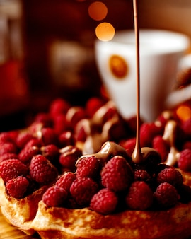 Maliny pod czekoladą na stole