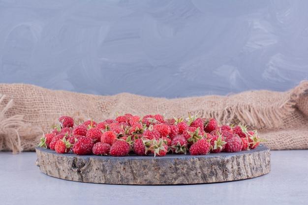 Maliny rozrzucone na drewnianej desce na marmurowym tle. zdjęcie wysokiej jakości