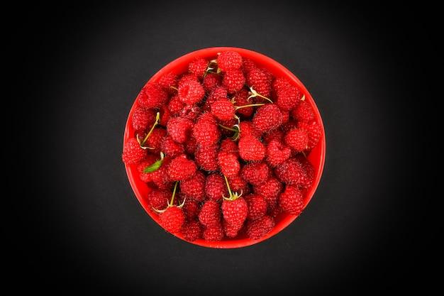 Maliny w czerwonym talerzu na czarnej przestrzeni. miska ze świeżych malin na różowym obszarze. skopiuj miejsce. minimalna koncepcja. ostre światło.