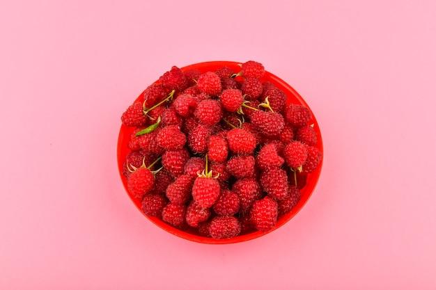 Maliny w czerwonym talerzu na różowym tle