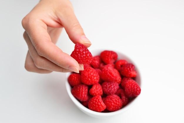 Maliny w misce w dłoni na białym tle izolacji kobieta ręka trzyma malinę czerwona malina w dłoni zdrowe odżywianie dieta wegetariańska koncepcja jedzenie i ludzie