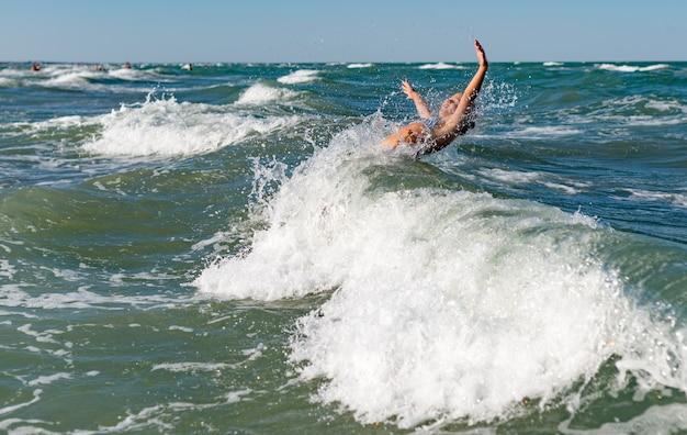 Mało śmieszne aktywne szczęśliwy dziewczyna przelewanie w hałaśliwe fale morza w słoneczny, ciepły letni dzień. koncepcja wakacje morze z dziećmi.
