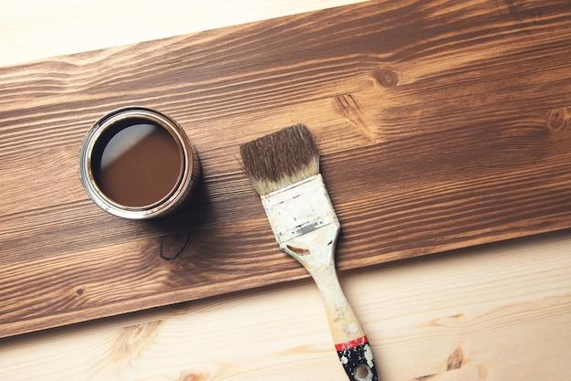 Malować pędzlem na brązowej powierzchni drewnianej