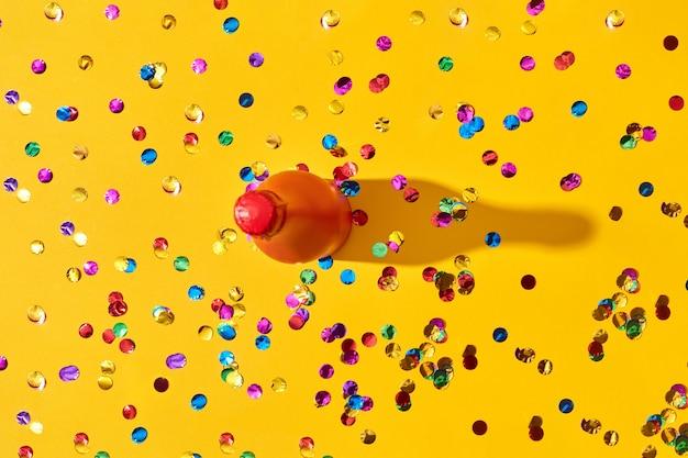 Malowana czerwona butelka na żółtym tle pokryta kolorowym konfetti z twardymi cieniami, kopia przestrzeń. karta z pozdrowieniami świątecznymi.
