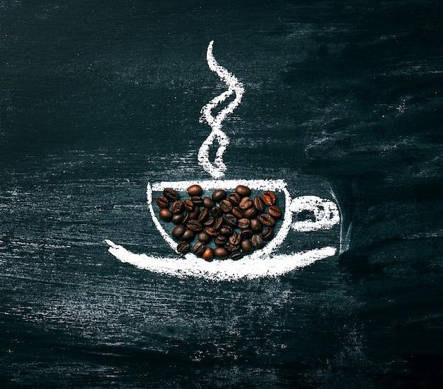 Malowana filiżanka kawy z ziaren kawy naturalnej na tablicy.