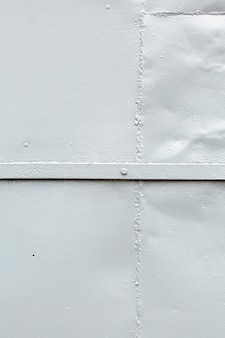Malowana metalowa powierzchnia z nitem i spawem