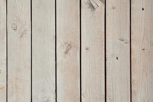 Malowana powierzchnia o jasnej, bielonej strukturze drewna z pionowymi deskami.