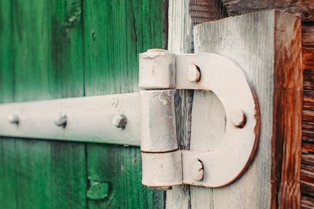 Malowane białe żelazne zawiasy na zielonych drewnianych bramach szopy z bliska. teksturowane szczegółowe tło z desek stodoły malowane jest żywą zieloną farbą z miejsca kopiowania. rustykalna konstrukcja.