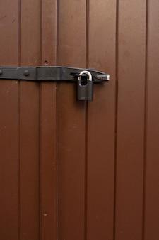 Malowane brązowe drzwi z wiszącym żelaznym zamkiem na zewnątrz. strzał zbliżeniowy