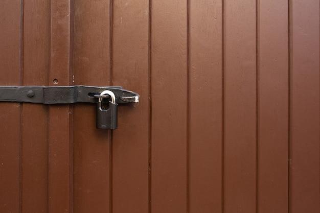 Malowane drewniane drzwi z wiszącym żelaznym zamkiem na zewnątrz. pusta przestrzeń