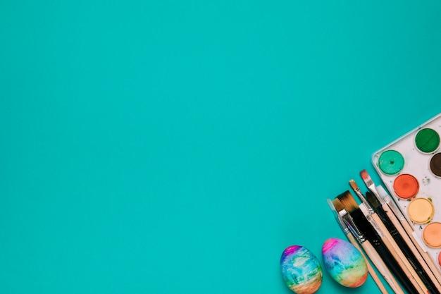 Malowane pisanki; szczotki i pole farby w kolorze wody na rogu zielonego tła