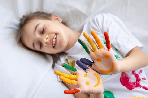 Malowane uśmiechy na dłoniach małej dziewczynki. śmieszne jasne rysunki na dłoniach dzieci.