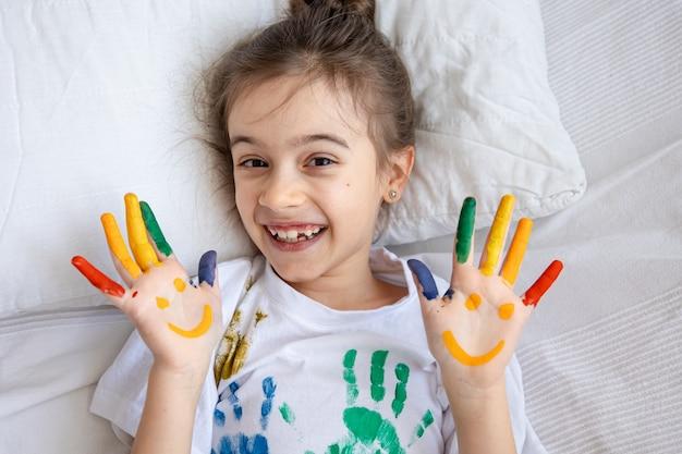 Malowane uśmiechy na dłoniach małej dziewczynki w koszulce z kolorowymi odciskami dłoni