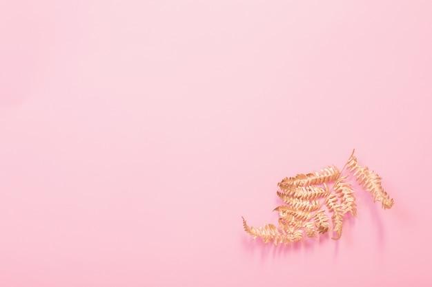 Malowane złote liście paproci na różowym tle papieru