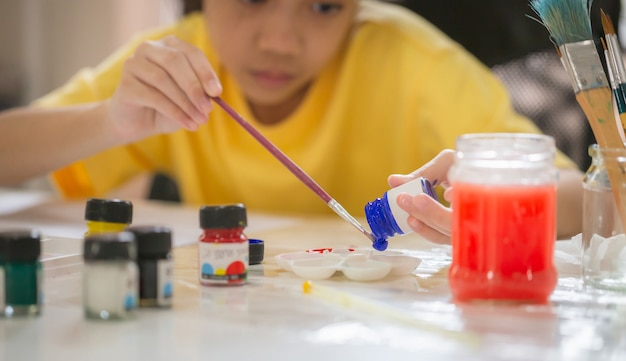 Malowanie dziecka przy stole w pokoju zabaw, dziewczyna z malowaniem pędzlem i paletą, nauka malowania online