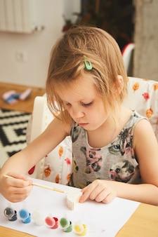 Malowanie dziecka. szczęśliwa dziewczyna w wieku przedszkolnym trzymając malowanie pędzlem